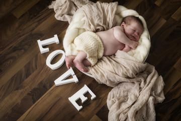 Newborn Baby schläft, mit Schriftzug Love