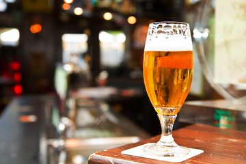 Glass of light beer on a dark pub