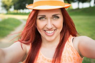 Beautiful redhead young woman taking a selfie