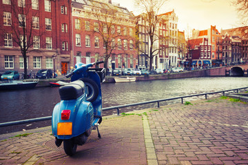 Poster Amsterdam Blue scooter stands parked on the canal coast in Amsterdam. Inst