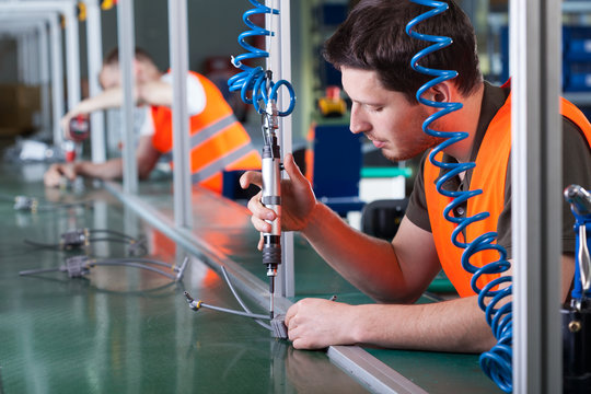 Men during precision work on production line