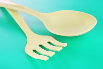 Plastic kitchen utensils on green background