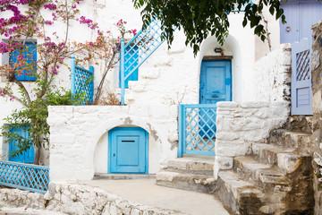 Fototapete - Typisch griechischer Baustil auf den Kykladen mit blauen Türen.