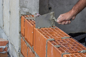 Construction worker using trowel on a hollow clay block wall