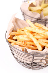 Tasty french fries in metal basket and potato chips, isolated