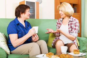 women colleagues drinking tea and chatting during coffee break