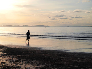 Silhouette of a man running in the beach during sunset