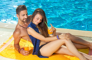 Young couple sunbathing and drinking cocktails.