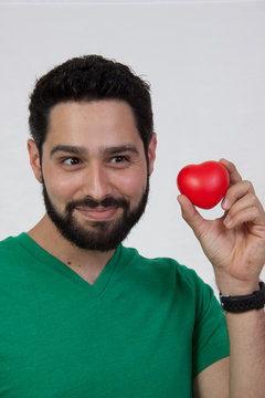 young bearded man holding heart