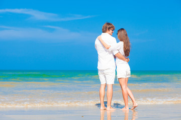 young couple in white hugging at tropical beach