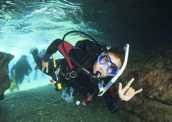 Scuba diver enters underwater cave