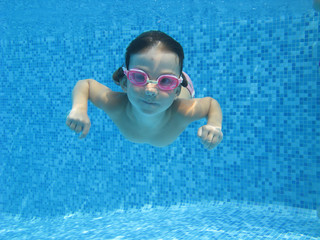 Happy active underwater child swims in pool, kids sport