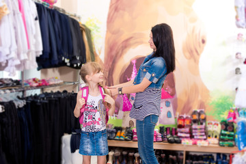 Cute beautiful little girl with her mother to buy clothes in sho