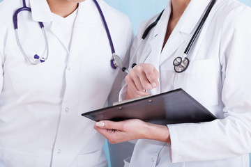 Doctors in medical white apron with stethoscopes and clipboard