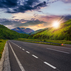 asphalt road in mountains at sunset