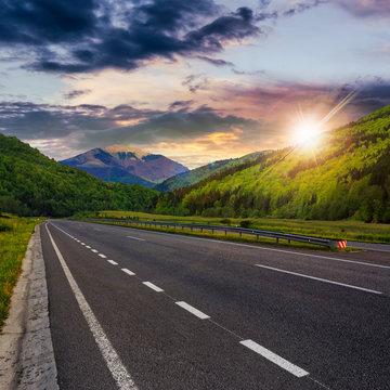 asphalt road in mountains at sunset