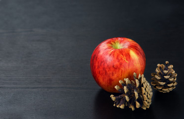 Pine cones and apple on black wooden background