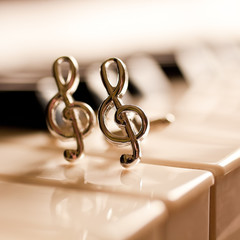 Fototapete - Ornaments in the form of a treble clef on piano keyboard