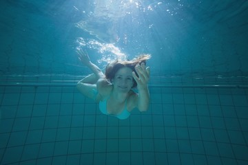 Pretty brunette smiling and offering her hand underwater