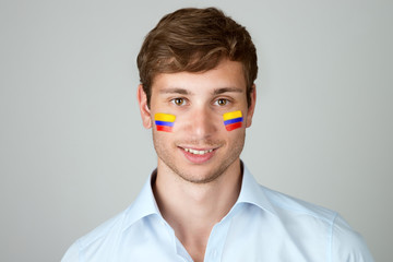 young handsome man with flag of Colombia painting at face