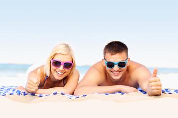 Happy couple sunbathing at the beach
