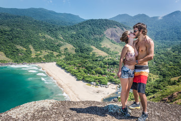 Beautiful couple kissing at a stone cliff, Brazil tropical islan