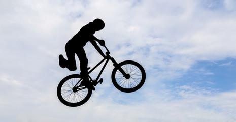 Silhouette of a man doing an jump with a bmx bike.