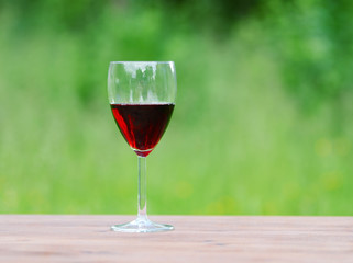Glass of wine on green nature background.