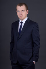young business man in suit over grey