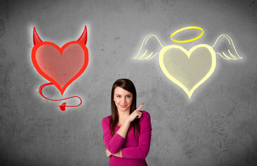 Woman standing between the angel and devil hearts