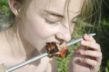 Girl with pleasure eats a shish kebab
