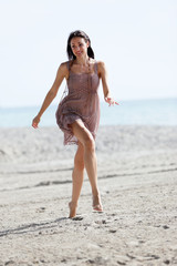 Stock image woman prancing on the sand