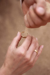 beautiful hand with wedding-ring and sand