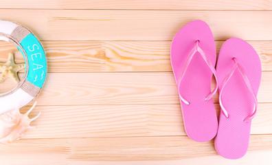 Bright flip-flops on wooden background