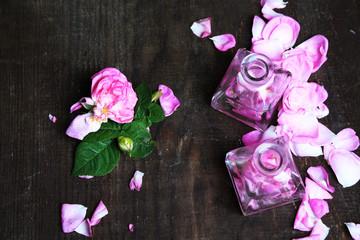 Rose oil in bottles on color wooden background