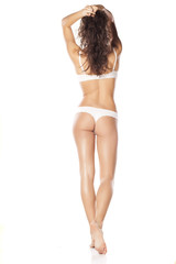 back view of pretty young woman posing in white lingerie