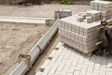 Neue Pflastersteine aus Beton werden in einem Kiesbett verlegt