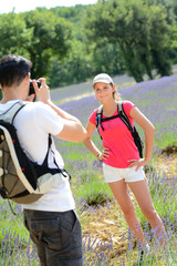 young man taking picture of girlfriend trekking summer vacation