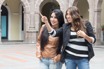 two latin girls smiling and pointing a place