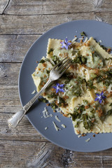 italian pasta ravioli with borage, flowers, sage on rustic table