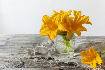 zucchini flowers on water glass on rustic table with napkin