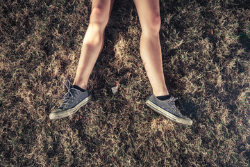 The legs of a young woman lying in th egrass