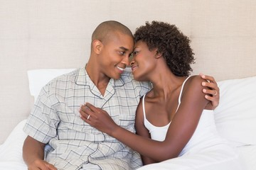 Happy couple sitting on bed cuddling