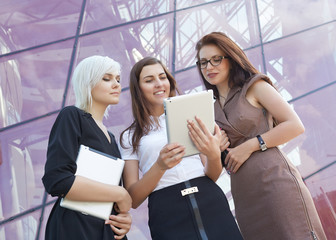 a group of businesswomеn from tablets on the street