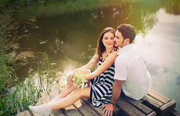 sensual romantic couple in love on pier at the lake in sunny day