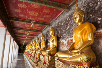 golden buddhas lined up along the wall in temple