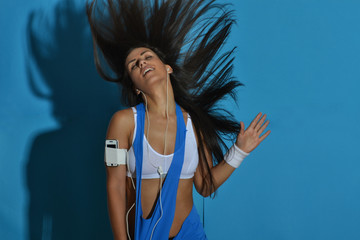 beautiful fitness woman dancing  against the blue background