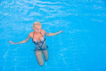 blonde woman enjoying the pool at the resort