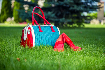 Fotobehang Picknick Shoes and women's handbag lay on the grass, women's shoes