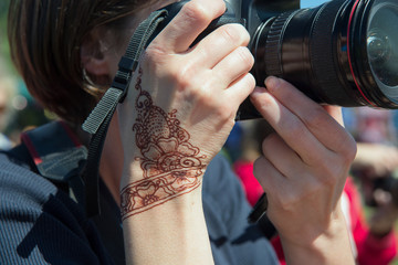 young woman photographer with henna ornament tattoo on her hand